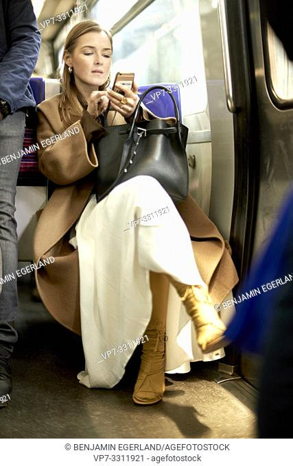 fashionable blogger woman texting with smartphone in metro, using public transportation, checking news at phone, during fashion week, in city Paris, France