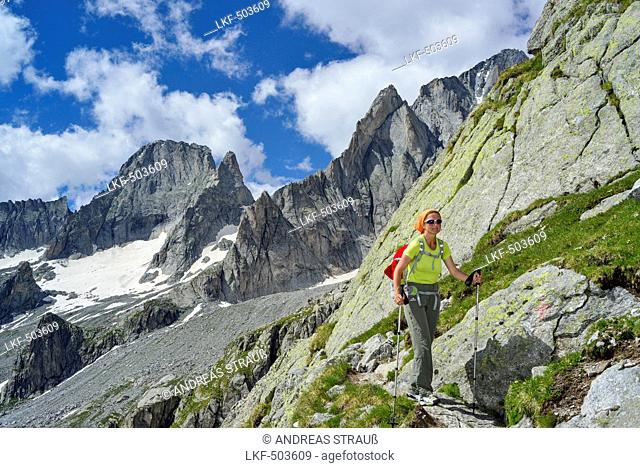 Woman hiking with Piz Badile in background, Sentiero Roma, Bergell range, Lombardy, Italy