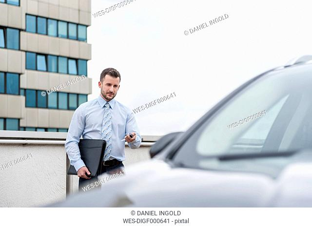 Businessman opening car on parking lot