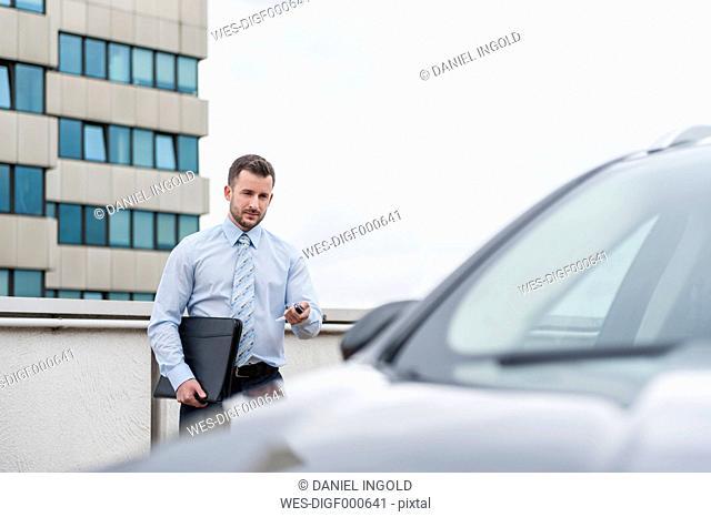 Businessman opening car on parking lot