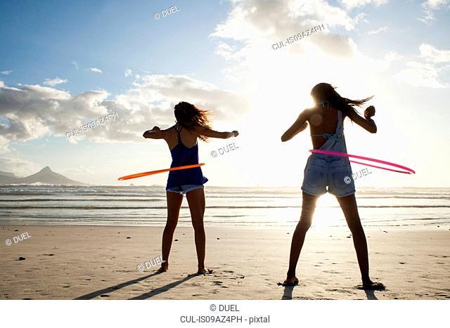 Rear view of women on beach using hula hoops