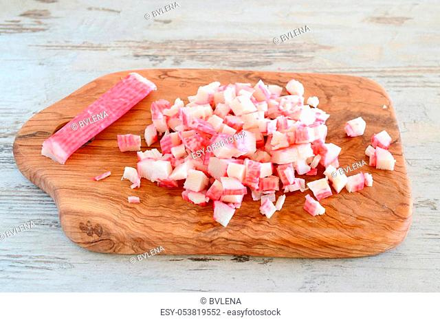 Crab sticks being cut on a olive wood cutting board. step by step cooking