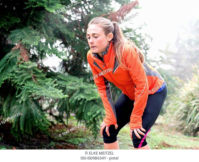 Exhausted female runner bending forward with hands on knees in park