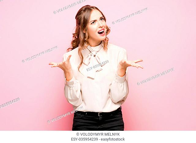 The serious frustrated young beautiful business woman on pink studio background