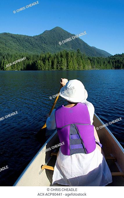 Woman paddling canoe on nKlein Lake near Egmont, , Sunshine Coast, British Columbia, CanadaBritish Columbia, Canada