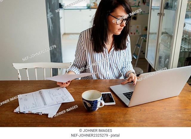 Woman using laptop and doing paper work