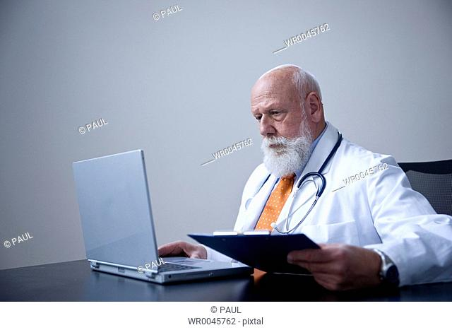 Male doctor using laptop