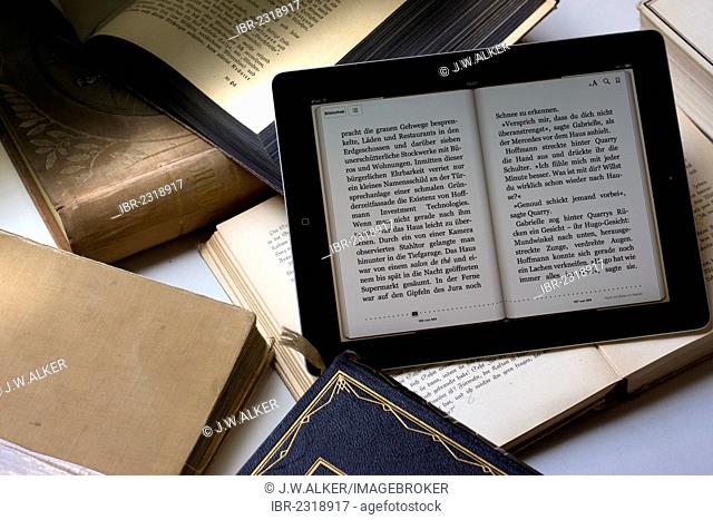 E-book reader beside old books, Germany