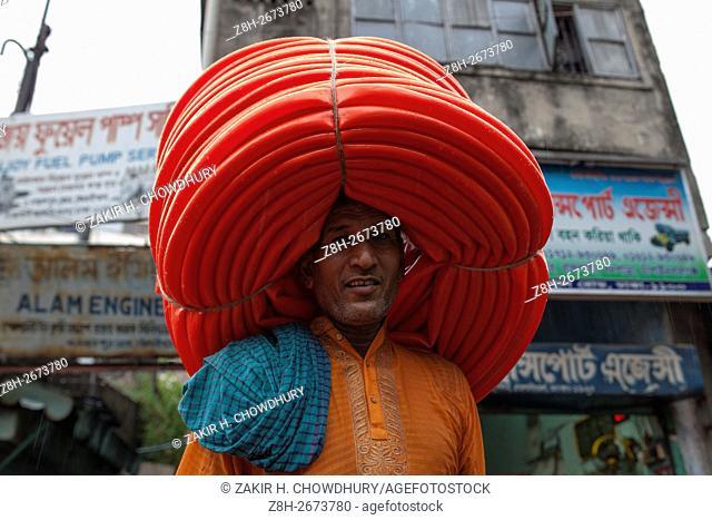 DHAKA, BANGLADESH - JUNE 07 : A labor carrying plastic pipe on his head in Dhaka, Bangladesh on June 07, 2016