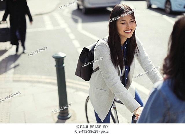Smiling young woman commuting, riding bicycle on sunny urban sidewalk