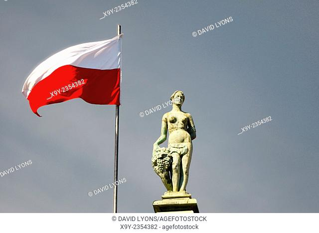 Gdansk Poland. Polish flag and statue on top of The Court of Artus in the Old Town main street of Dlugi Targ