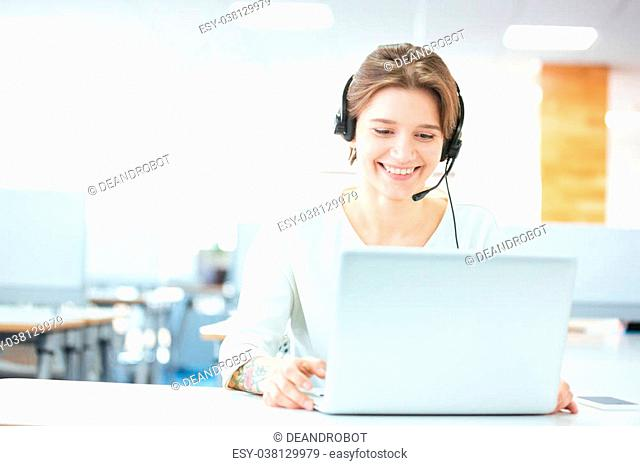 sitting and working with laptop and headset