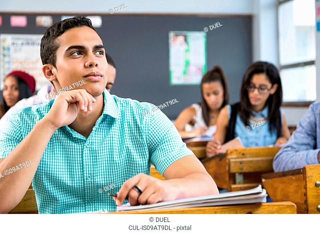 Portrait of male student, sitting at desk in classroom