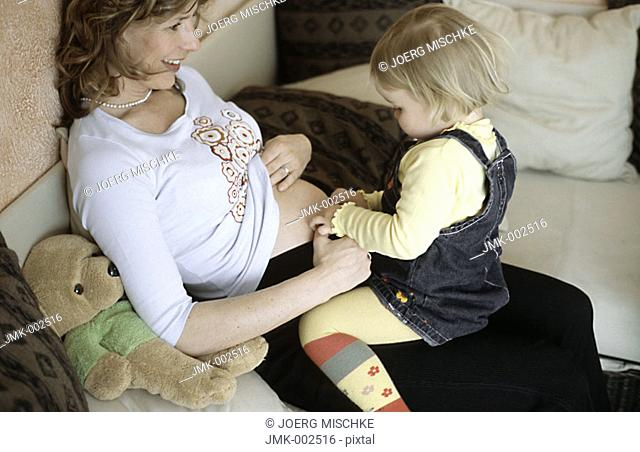 A young pregnant woman, 25-30 30-35 35-40 years old, sitting on the sofa with her little daughter, 1-5 years old