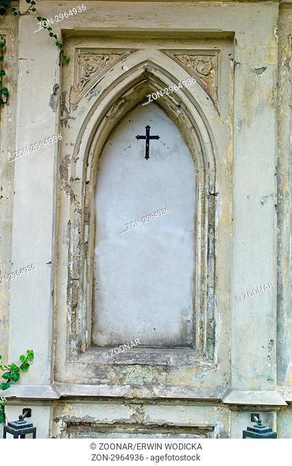 Ein Grabstein auf einem Friedhof. Mit Efeu überwuchert