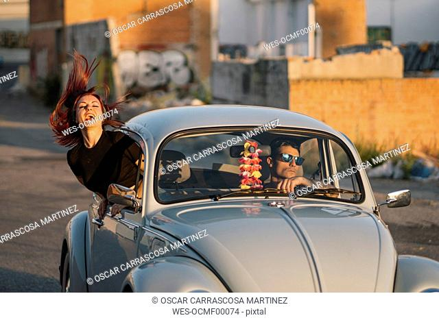 Couple driving in a vintage car, woman banding out of window
