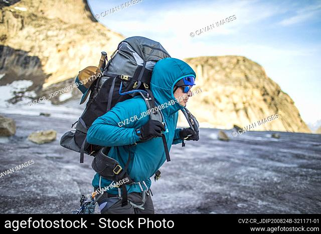 Mountaineer lifts heavy backpack onto shoulders while crossing glacier