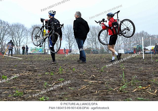 15 April 2018, Germany, Steimbke:Three men, two of them bicycle racers who carry their bikes, walk across the field during the 36th German Power Ploughing...