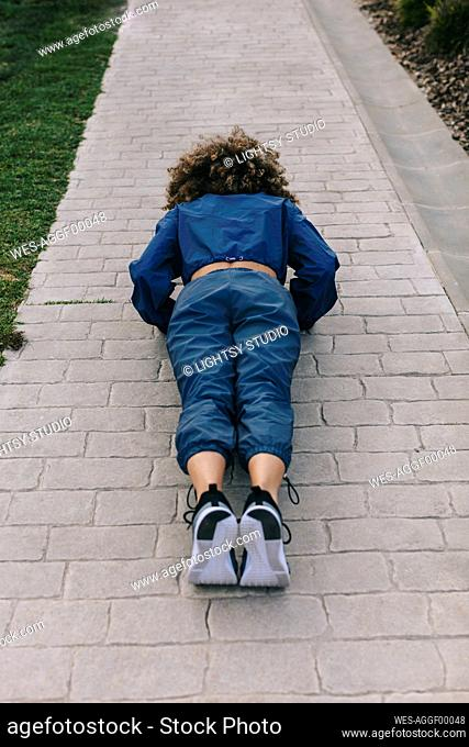 Young woman doing push ups on a path