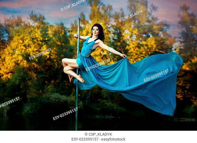 Girl high pole to dance her dress develops wind