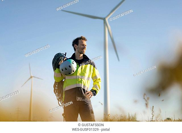 Technician standing in a field at a wind farm with climbing equipment