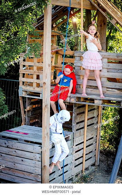 Three kids with superheroes costumes playing on their homemade tree house