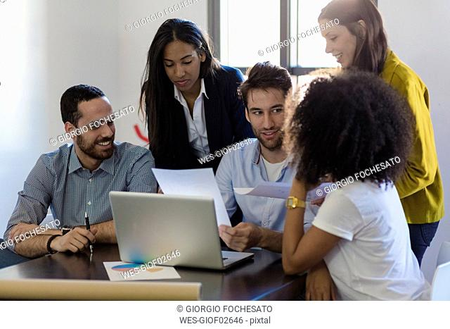 Business people sharing laptop in office
