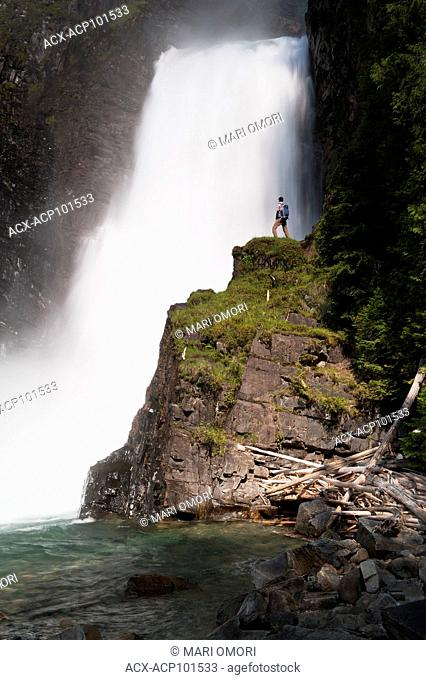 A hiker stands on a cliff beside Wilson Creek Falls in Goat Range Provincial Park. Model Release signed