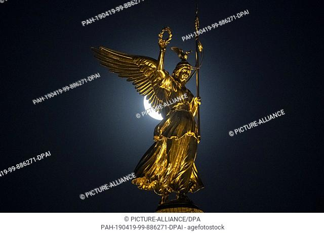 """dpatop - 18 April 2019, Berlin: The moon shines behind the statue of Victoria (""""""""Goldelse"""""""") on the Victory Column. Photo: Paul Zinken/dpa"""