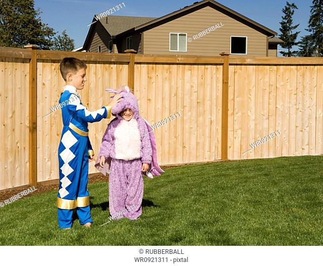 Girl and boy in yard in halloween costumes