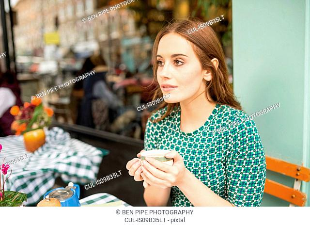 Woman at pavement cafe holding teacup looking away