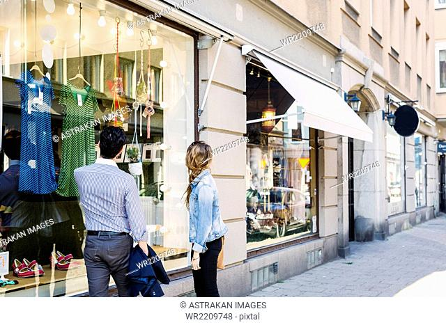 Couple looking at clothes displayed on store window