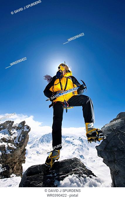 Mountaineer with ice axe and oxygen above the clouds