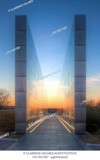 Twilight colors in the western sky provide a colorful background and reflections on the New Jersey 9/11 Empty Sky Memorial