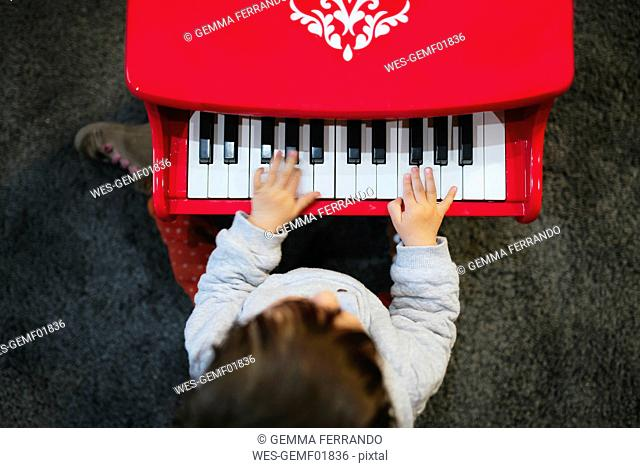 Baby girl playing toy piano at home, from above