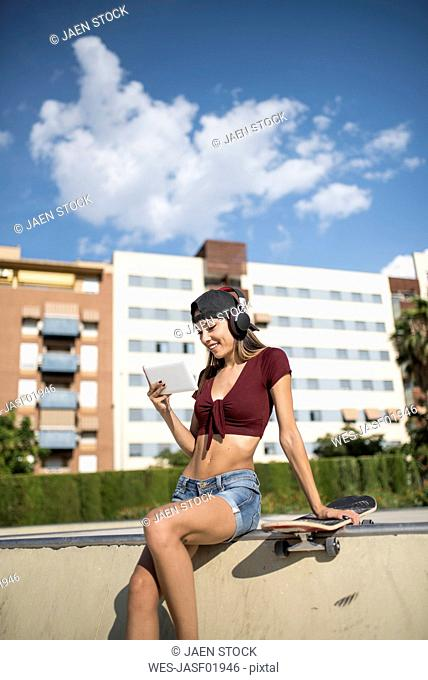 Young pretty woman sitting on wall of skatepark, listen music, using digital tablet