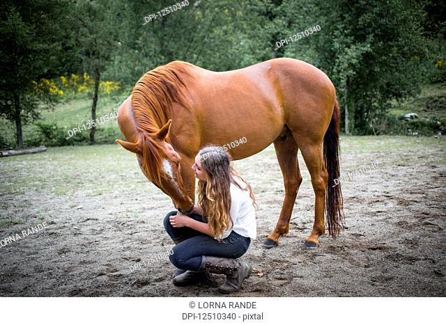 A teenage girl crouching down to talk to and care for her horse; British Columbia, Canada