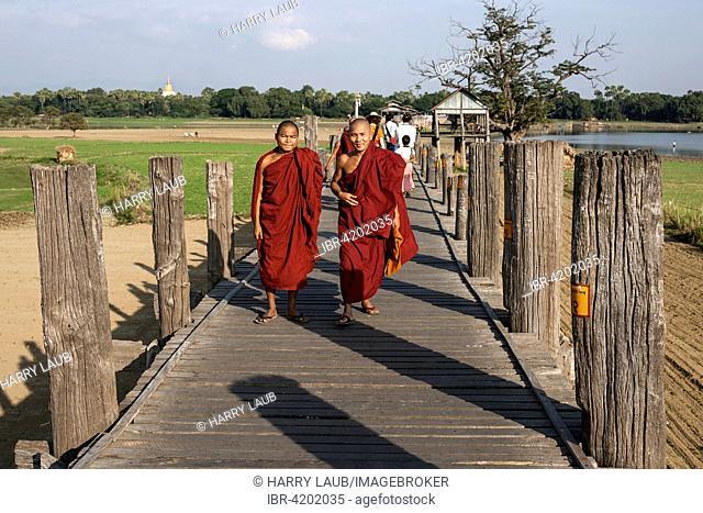 Two Buddhist monks walking on the U Bein Bridge, Amarapura, Division Mandalay, Myanmar
