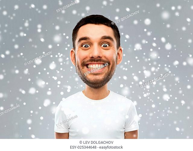 expression, winter, christmas and people concept - smiling man with funny face over snow on gray background (cartoon style character with big head)