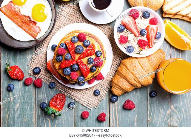 Breakfast with pancakes , eggs , croissants , coffee , berry , orange juice and bread