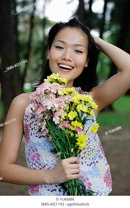 Young woman holding bouquet of flowers, hand on head, smiling at camera