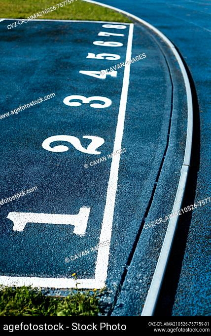 Close-up of white numbers on blue running track