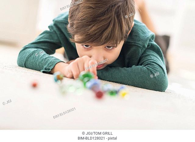 Hispanic boy playing with marbles on bedroom floor
