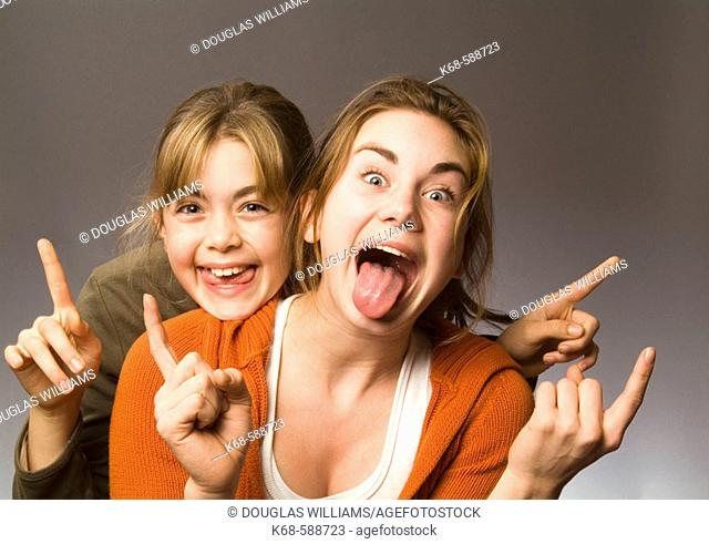 Girls, 10 and 15 playing, making faces