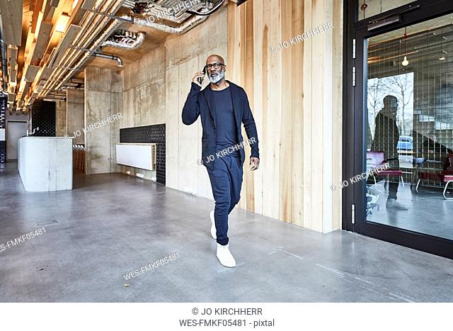 Mature businessman on cell phone walking in modern office