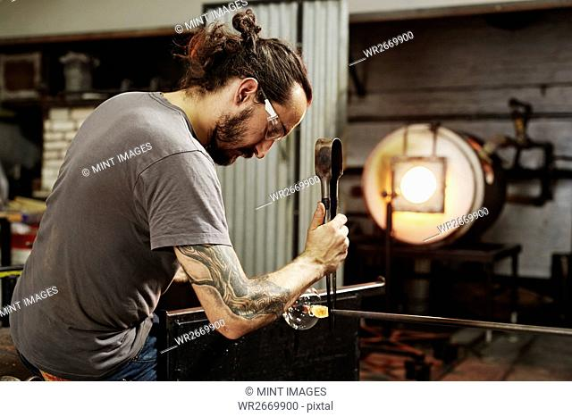 A glassblower with pliers working on a piece of glass