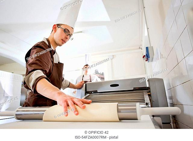 Baker rolling dough in kitchen