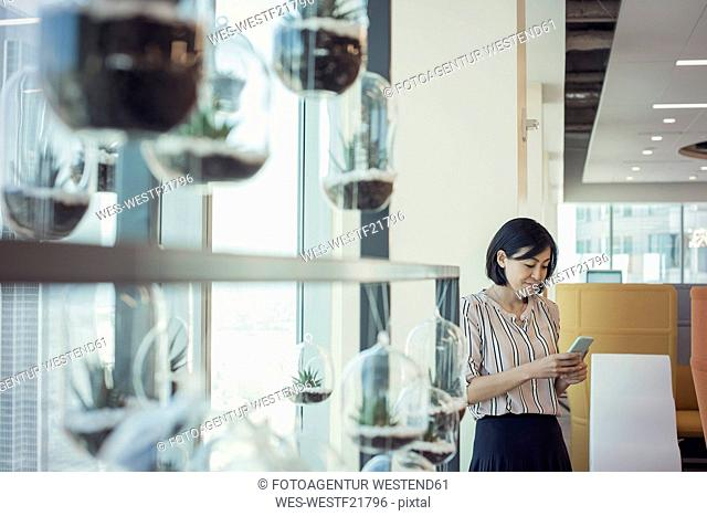 Businesswoman standing in office using smart phone