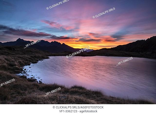 Amazing sunrise coloring the whole sky while the wind gently moves the surface of Lake Arcoglio - Valmalenco, Valtellina Sondrio, Lombardy, Italy Europe
