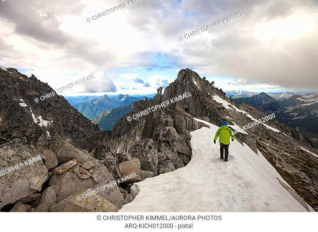 Photograph with rear view of mountain climber approaching south summit of Mount Rexford, Chilliwack, British Columbia, Canada